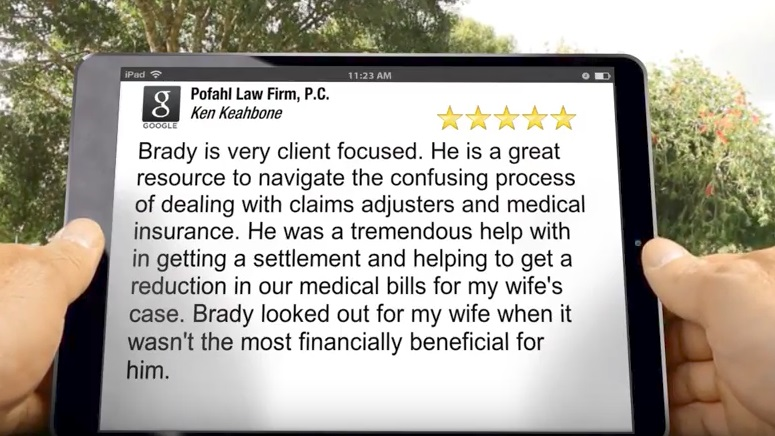 A person holding an iPad reading a five star review of Pofahl Law Firm, P.C. for a job well done on another car accident case.
