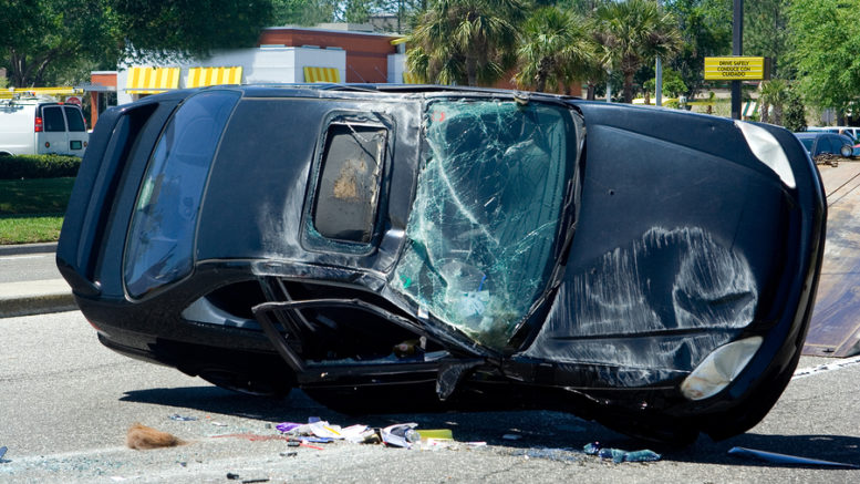 A black car had an accident was tilted on the road with broken window glass,