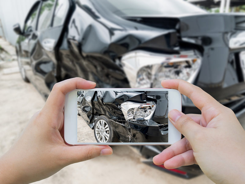A person captures a picture of his car wreck due to a car accident.