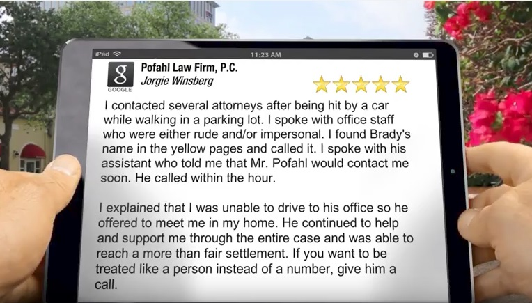 A person holding an iPad reading a five star review of Pofahl Law Firm, P.C. for a job well done on another pedestrian accident case.