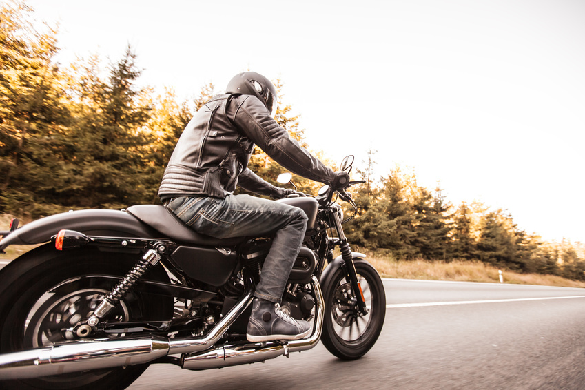 A person wearing a black helmet riding a black motorcycle on the road.
