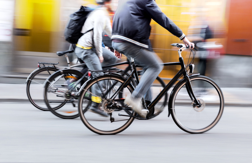 Three people are riding a bicycle on a fast pace that may cause a bicycle accident.