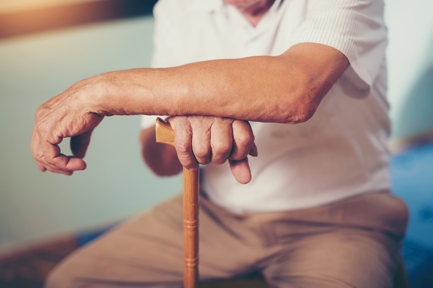 An old man sitting while holding his wooden crane and experienced nursing home abuse.