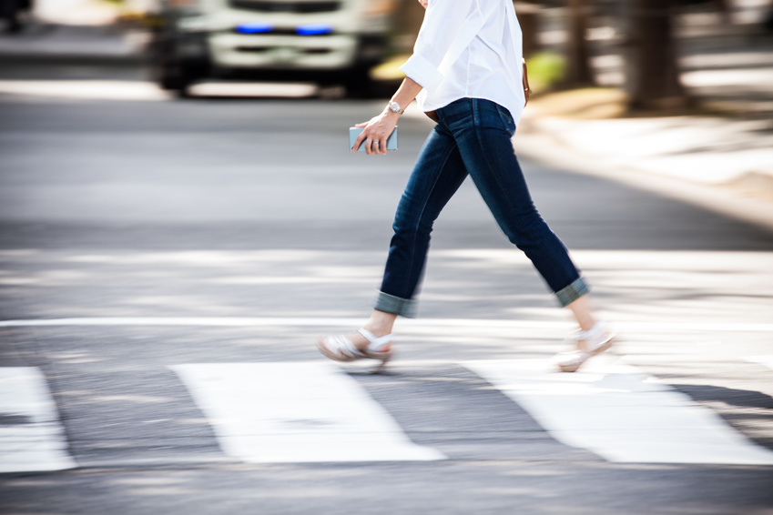 A person is crossing the pedestrian in a fast pace that may result a pedestrian accident if not careful.