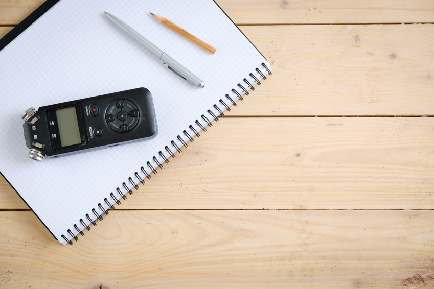 A recorder, a notebook, a pen, and a pencil used for getting a recorded statement of a person who experienced a car accident.