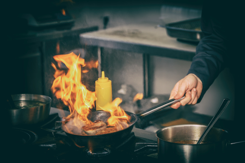 A person is cooking a meat with a fire blazing on the pan that may cause a burn injury.