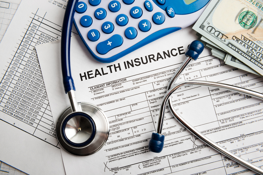 A health insurance form for injury settlements with a stethoscope, US money and a calculator beside it.