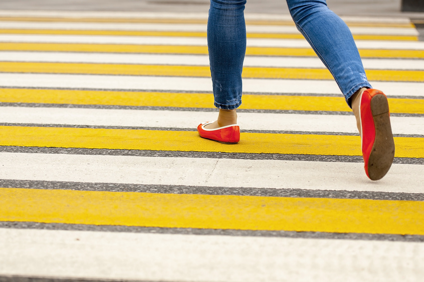 a woman crossing on a pedestrian lane with yellow and white painted on it