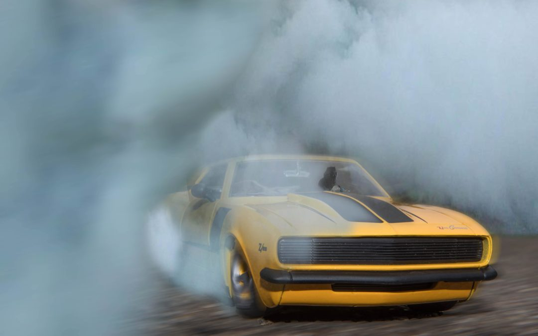 a yellow camaro car drifting in circular motion creating enough friction to produce smoke and tire marks
